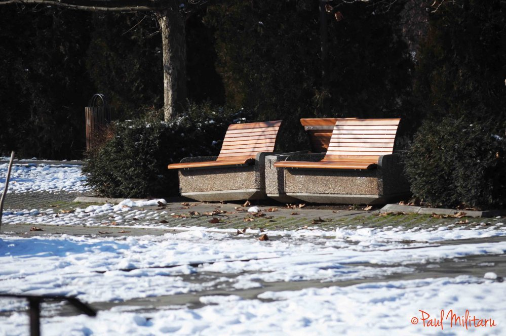 two empty benches and a little bit of snow
